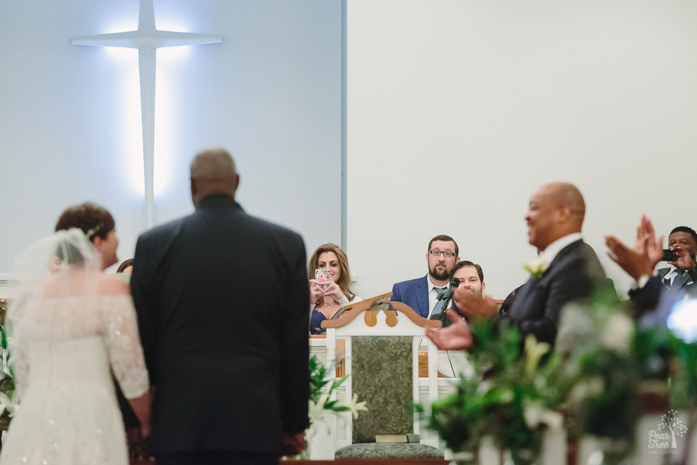 Family and friends clapping over marriage in church