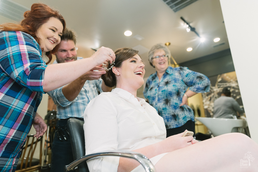 Bride surrounded by mom, sister, and hair stylist at Salon Kru