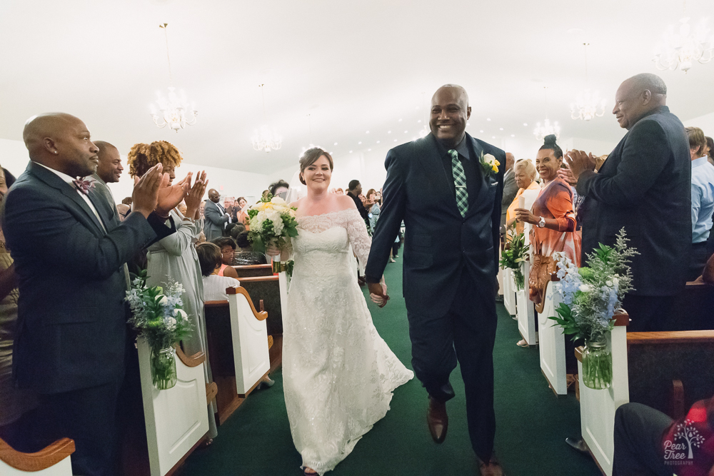 Bride and groom happily walking down aisle together after wedding